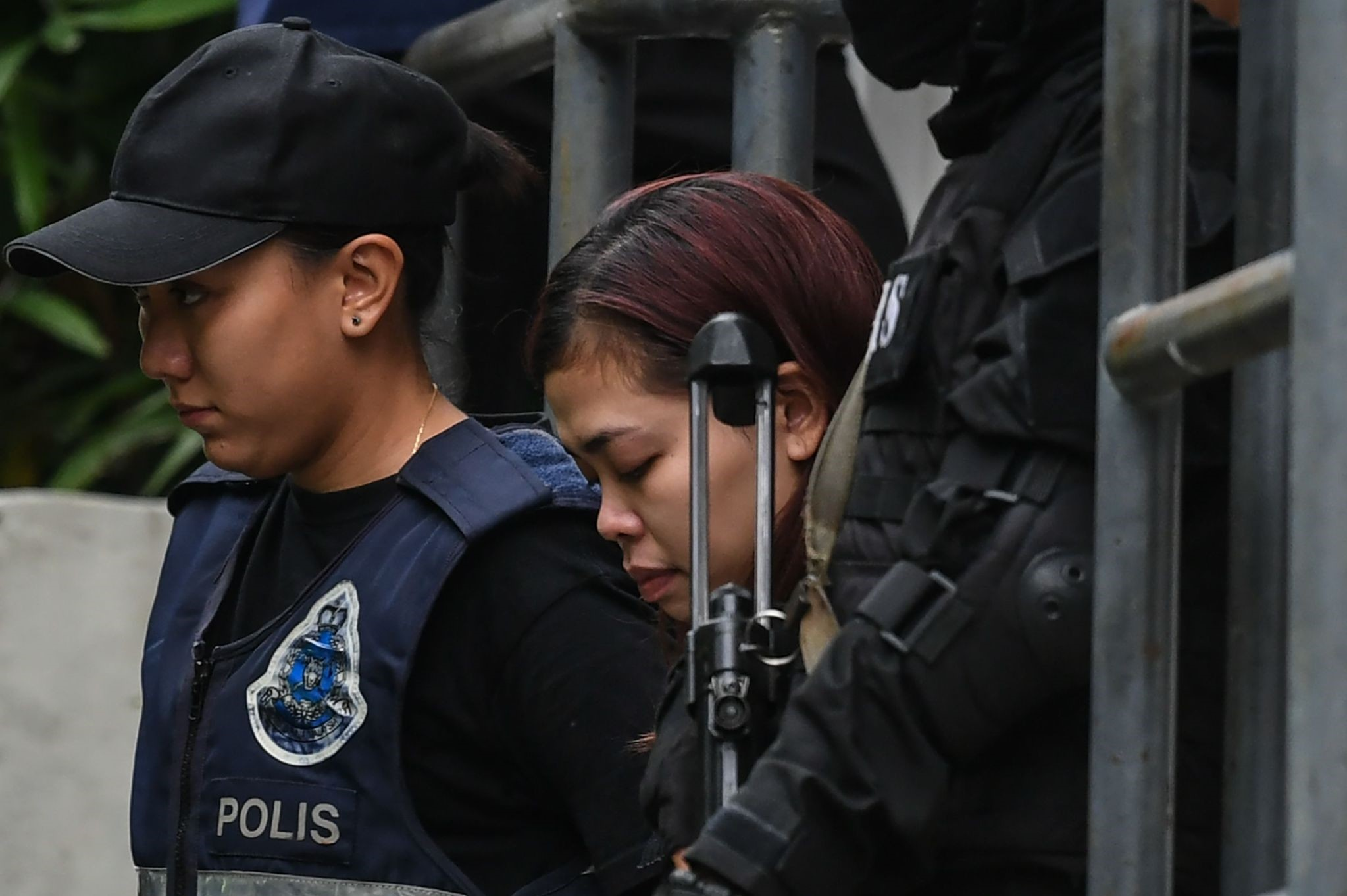 Indonesian national Siti Aisyah (C), 25, being escorted with a heavy police presence after a court appearance in Sepang. (AFP Photo)