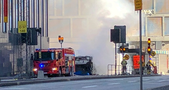 An emergency vehicle stands in front of the bus that exploded and caught fire in central Stockholm, Sweden on Sunday March 10, 2019 (AP Photo)