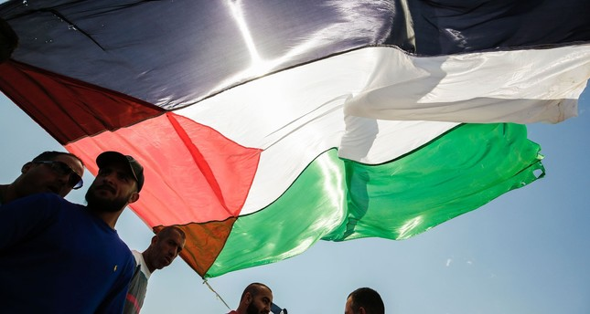 Palestinians gather by a large national flag during a demonstration near the West Bank city of Ramallah, on March 31, 2017. (AFP PHOTO)