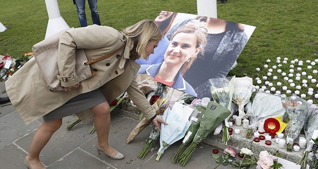 A woman leaves a floral tribute next to a photograph of murdered Labour Member of Parliament Jo Cox in Parliament Square, London, Britain June 17, 2016 (Reuters Photo)
