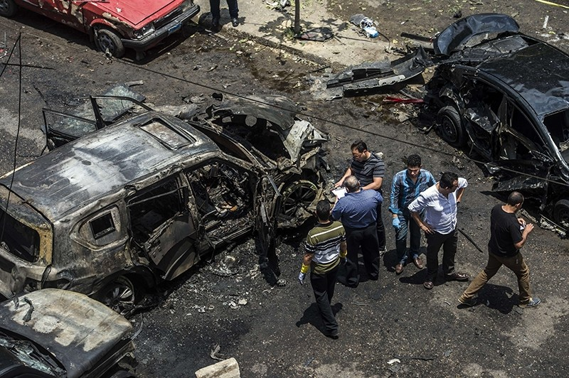 Forensic detectives gather at the site of a bomb that targeted the convoy of the Egyptian state prosecutor, Hisham Barakat, in the capital Cairo on June 29, 2015.  (AFP Photo)