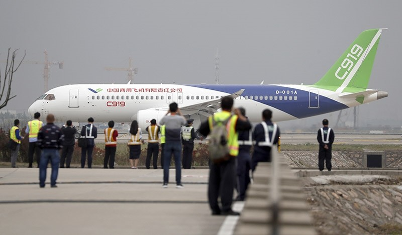 Spectators watch as a Chinese C919 passenger jet taxis for take-off on its first flight at Pudong International Airport in Shanghai, Friday, May 5, 2017. (AP Photo)