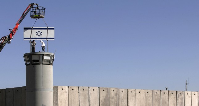 Workers place Israel's national flag atop a watchtower on the wall surrounding Israel's Ofer military prison near the occupied West Bank city of Ramallah Dec. 19, 2006. Reuters Photo