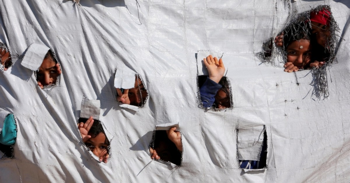 Children look through holes in a tent at al-Hol displacement camp in Hasaka governorate, Syria, April 2, 2019. (Reuters Photo)