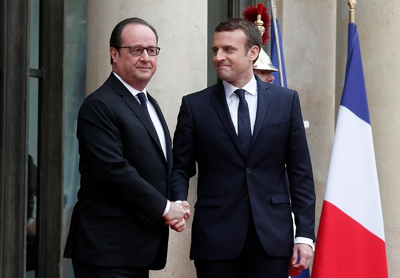 Outgoing French President Francois Hollande greets President-elect Emmanuel Macron who arrives to attend the handover ceremony at the Elysee Palace in Paris, France, May 14, 2017 (Reuters Photo)