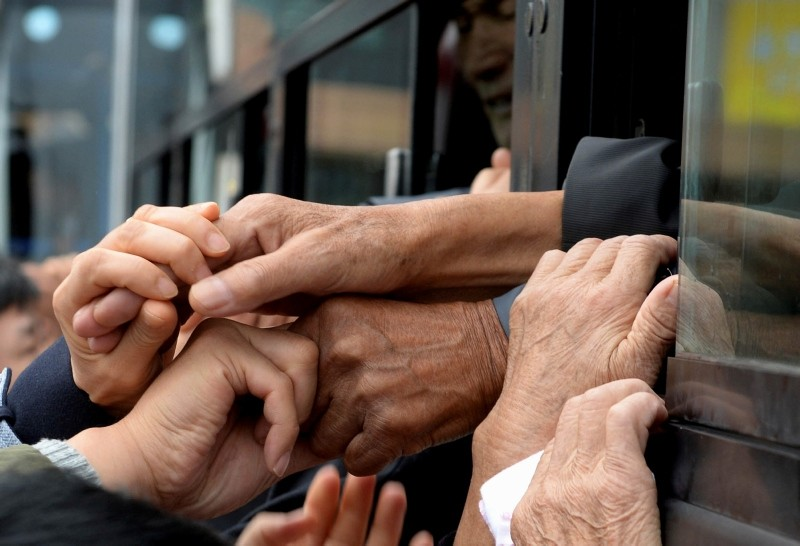 In this Oct. 22, 2015, file photo, South Koreans and their North Korean relatives on a bus grip their hands each other to bid farewell after the Separated Family Reunion Meeting at Diamond Mountain resort in North Korea. (AP Photo)