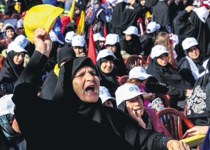 Hezbollah supporters listen to Lebanon's Hezbollah leader Hassan Nasrallah delivering a speech via a big screen during a gathering to commemorate the u201cAl-Quds (Jerusalem) International Dayu201d, Maroun Al-Ras, Lebanese-Israeli border, June 8.