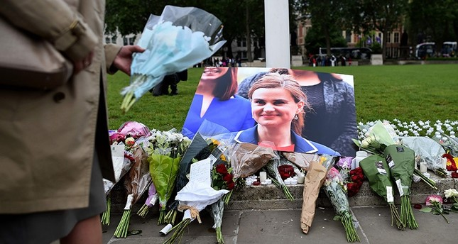 Floral tributes sit by a picture of slain Labour MP Jo Cox in Parliament Square, central London on June 17, 2016 AFP Photo