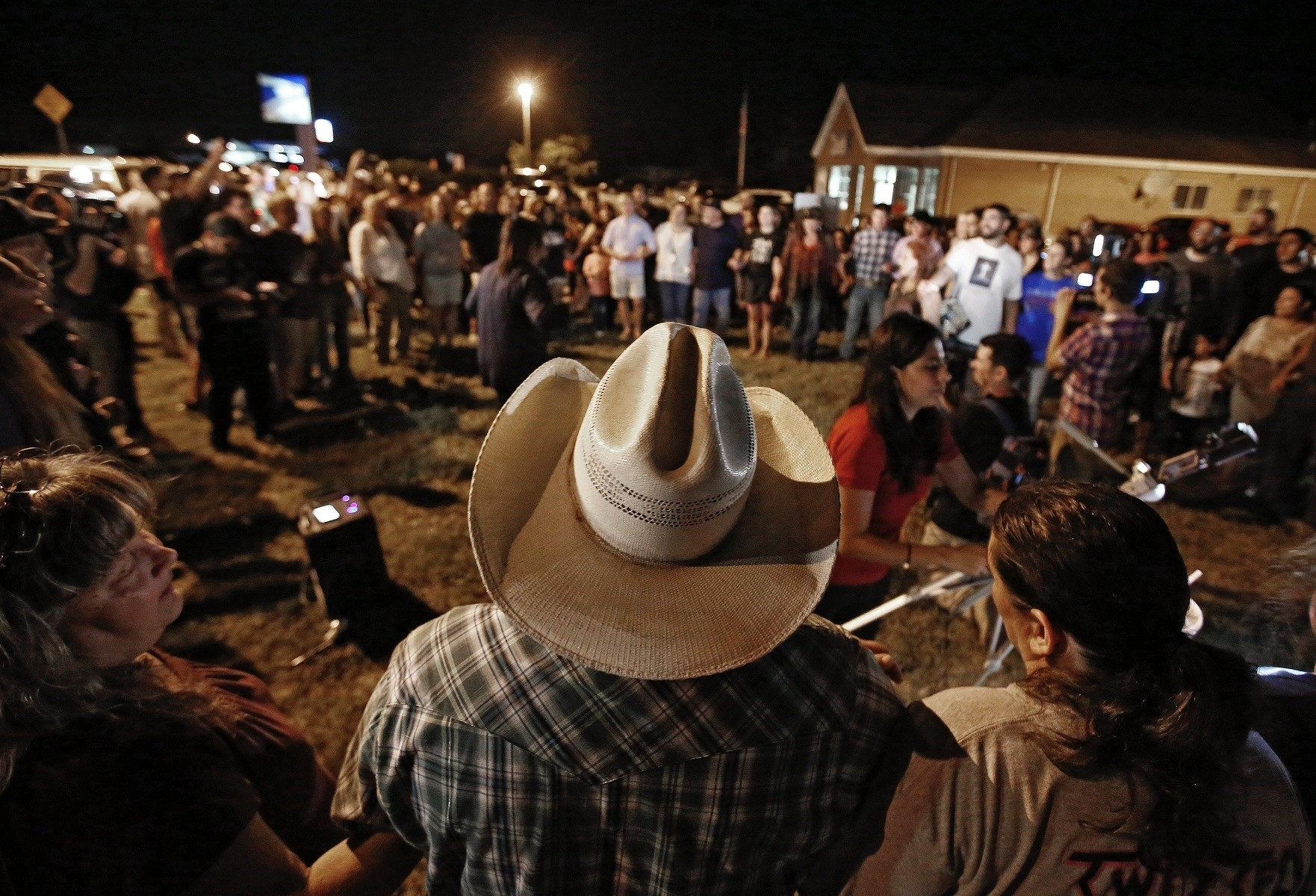People attend a vigil near where a mass shooting took place at the First Baptist Church, which killed 26 and wounded some 20 others, Sutherland Springs, Texas, Nov. 5.