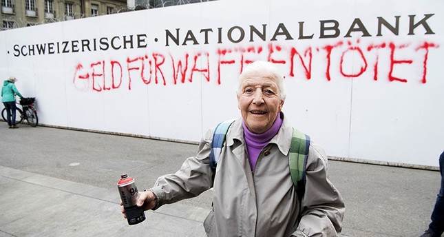 86-year-old activist Louise Schneider poses for media after spraying the words Money for Weapons Kills (in German Geld Fuer Waffen toetet) on a wall of the Swiss National Bank. (AP Photo)