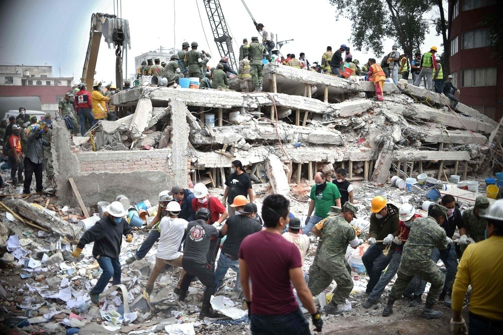 Rescuers, firefighters, policemen, soldiers and volunteers search for survivors in a flattened building in Mexico City on Sept. 20, a day after a strong quake hit central Mexico.