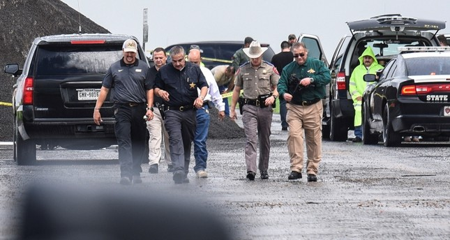 Law enforcement officers gather near the scene where the body of a woman was found near Interstate 35 north of Laredo, Texas on Saturday, Sept. 15, 2018. (AP Photo)