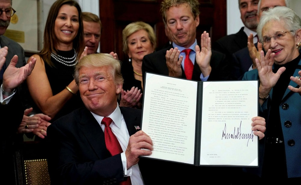 U.S. President Donald Trump smiles after signing an executive order at the White House in Washington, Oct. 12.