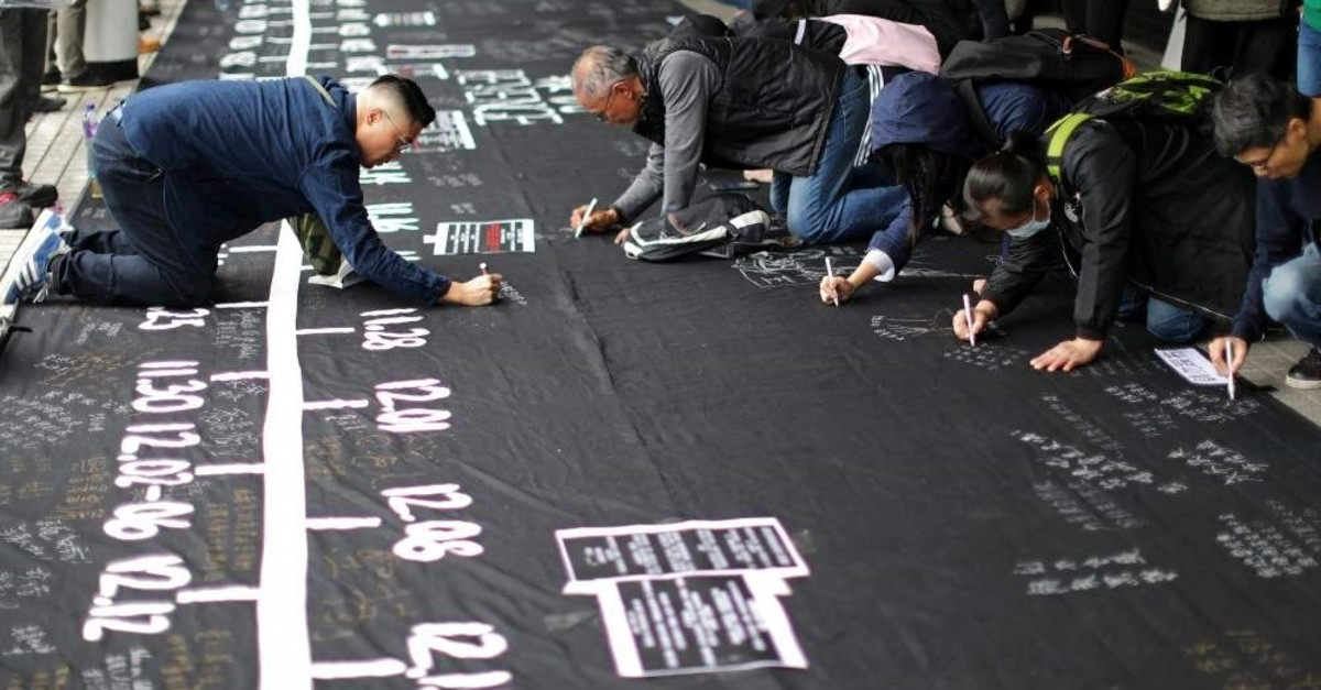 People write messages on a memorial timeline banner during an anti-government rally at Edinburgh Place, Hong Kong, Dec. 29, 2019 (REUTERS Photo)