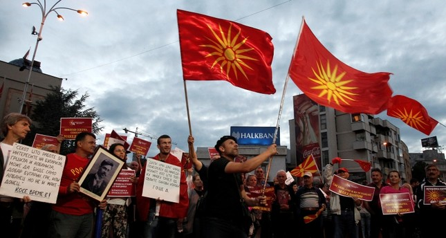 Opponents of the deal between Greece and Macedonia on the latter country's new name North Macedonia hold banners and wave the former national flag, while protesting outside the parliament in Skopje, Macedonia, Saturday, June 23, 2018.  (AP Photo)