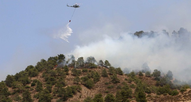 A helicopter drops water on a forest fire in the Cypriot village of Eyrixou in the Trodos mountain area on June 20, 2016. AFP Photo