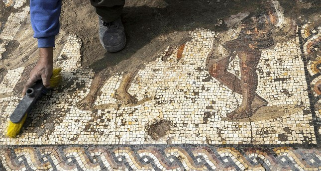 A worker from the Israeli Antiquity Authority (IAA) cleans a rare Roman mosaic from the 2nd–3rd centuries at the Israeli Caesarea National Park on February 8, 2018. (AFP Photo)