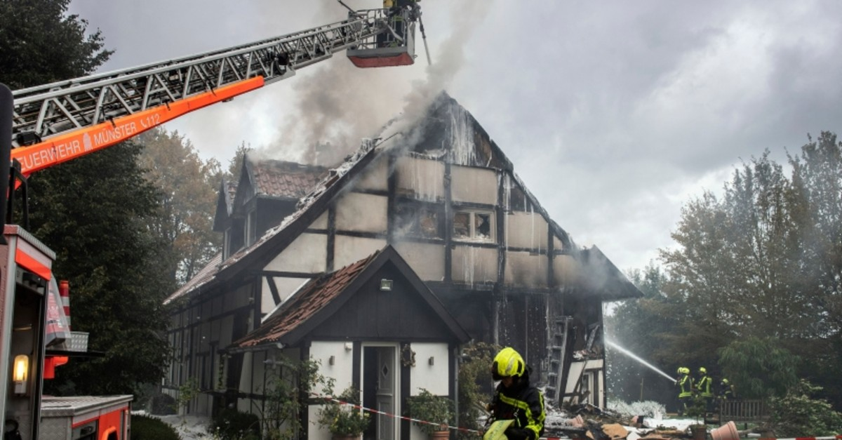 Firefigthers extinguish a fire in a house in Muenster, Germany, Wednesday, Sept. 18, 2019. Two women and a police officer where injured by an exploion inside the house (AP Photo)