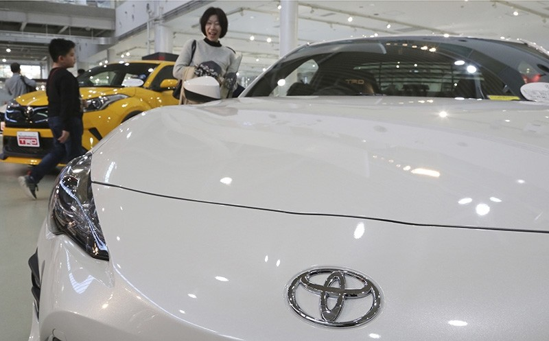 In this Nov. 13, 2017 photo, visitors take a look at a Toyota car at its showroom in Tokyo. (AP Photo)