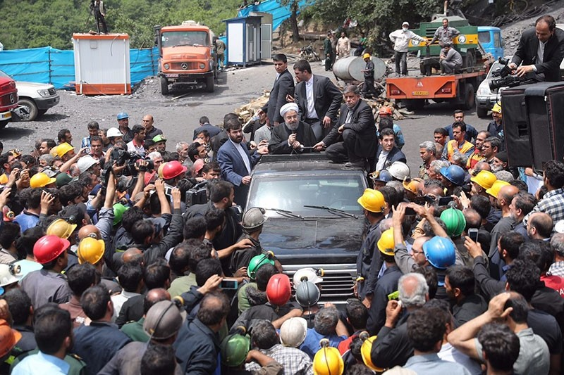 A handout picture provided by the office of Iranian President Hassan Rouhani on May 7, 2017 shows him (C) sitting through the roof of a car, visiting and speaking with coal miners and rescue workers in Azadshahr, in northern Iran. (AFP Photo)