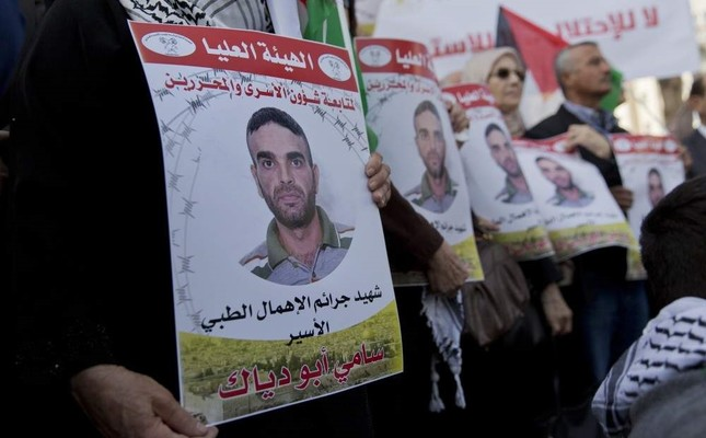 Protesters fly Palestinian flags and carry posters with pictures of Palestinian prisoner Sami Abu Diak, who is in an Israeli jail, Ramallah, Nov. 26. 2019. (AP Photo)