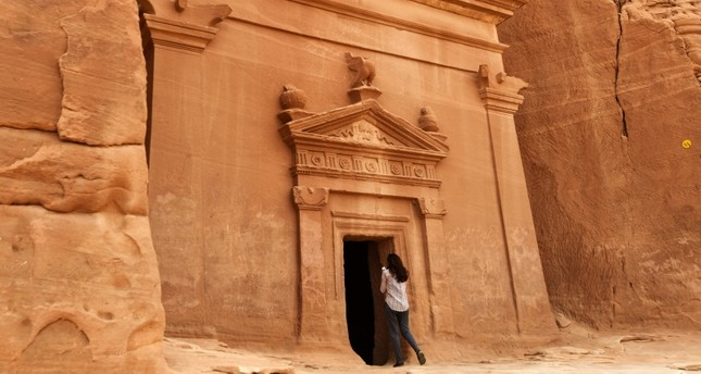In this file photo taken on March 31, 2018 a journalist takes a photo of a tomb at Madain Saleh, a UNESCO World Heritage site, near Saudi Arabia's northwestern town of al-Ula. (AFP Photo)