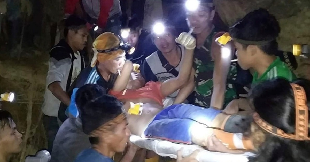 In this undated photo released by Indonesian Search And Rescue Agency (BASARNAS) rescuers evacuate a survivor from a collapsed gold mine in Bolaang Mongondow, North Sulawesi, Indonesia. (AP Photo)