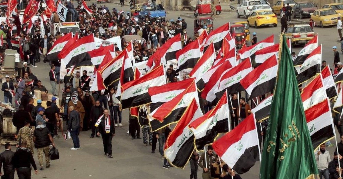 People hold national flags and chanting religious slogans march in Tahrir Square in Baghdad, Iraq, Friday, Dec. 6, 2019. (AP Photo)