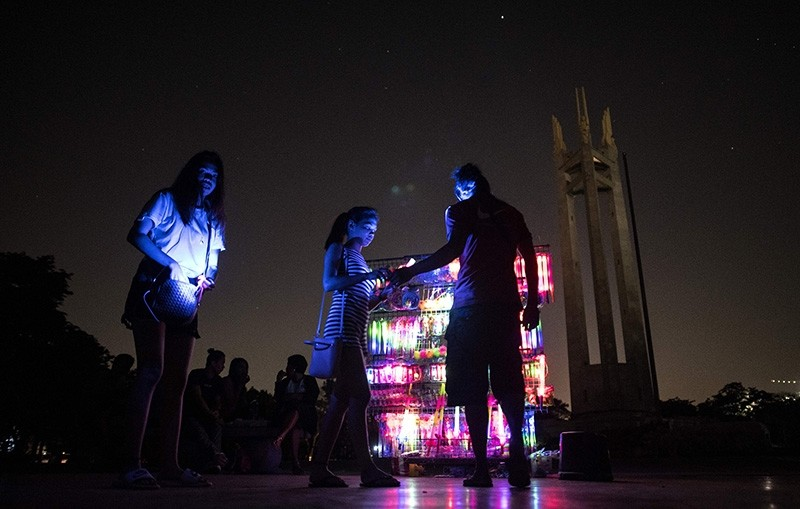 A vendor sells light-up yoys in front of the Quezon Memorial Shrine after the switching off lights for the Earth Hour environmental campaign in Manila on March 24, 2018 (AFP Photo)