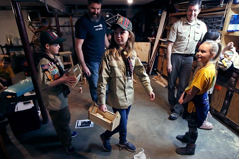 In this March 1, 2018, file photo, Tatum Weir, center, carries a tool box she built as her twin brother Ian, left, follows after a Cub Scout meeting in Madbury, N.H. (AP Photo)