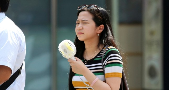 A woman holds a portable fan at a business district in Tokyo, Monday, July 23, 2018. (AP Photo)
