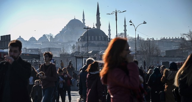 People walk in Istabul's Eminönü district in front of the Rustem Paşa (front) and Süleymaniye (back) mosques, Feb. 19, 2019.