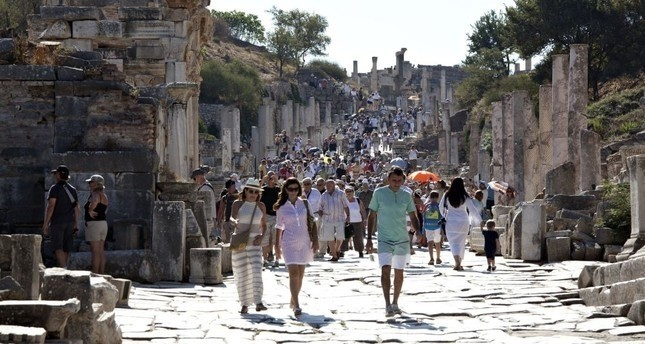 Tourists walking on u0130zmiru2019s Curetes Street, which is one of the main streets of Ephesus, connecting the Magnesia gate to the Koresos gate.