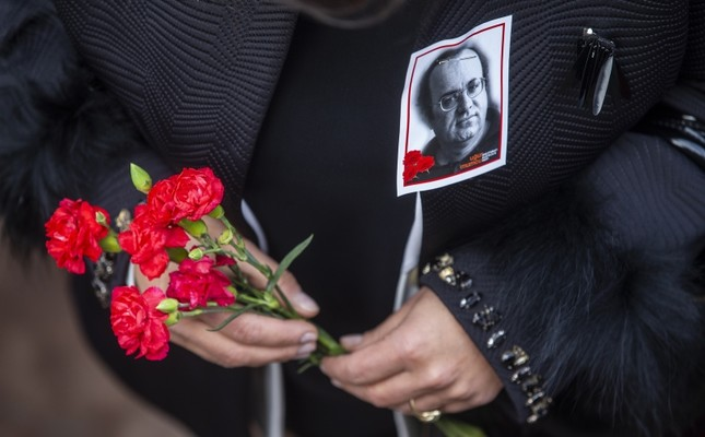 A woman with a photo of journalist Uğur Mumcu pinned to her coat holds flowers during a commemorative ceremony on the 26th anniversary of his assasination, in Ankara, Turkey, Thursday, Jan. 24, 2018. (AA Photo)