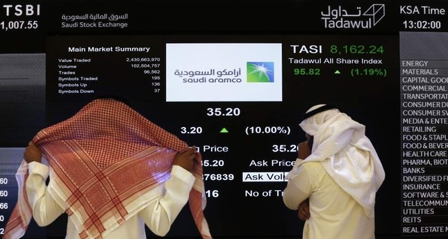 In this Dec. 11, 2019, file photo, the Saudi stock market officials watch the stock market screen displaying Saudi Arabia's state-owned oil company Aramco after the debut of Aramco's initial public offering IPO on the Riyadh's stock market in Riyadh, Saudi Arabia. AP Photo