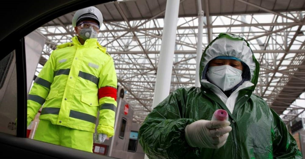 A medical worker and police officer stand at a checkpoint, Anqing, Feb. 6, 2020. (REUTERS Photo)