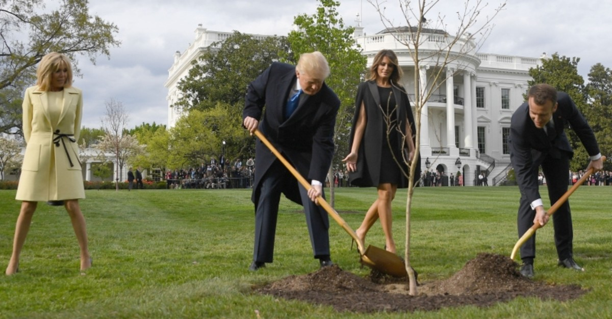 In this file photo taken on April 23, 2018 US President Donald Trump and French President Emmanuel Macron plant a tree watched by Trump's wife Melania and Macron's wife Brigitte on the grounds of the White House in Washington, D.C. (AFP Photo)