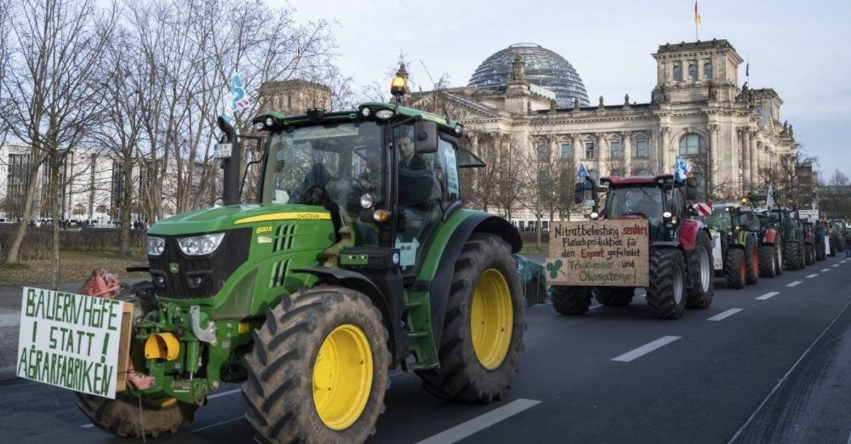 Farmers drive past the Reichstag building with their tractors in Berlin, Saturday, Jan.18, 2020. (AP Photo)