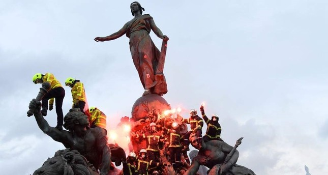 Firefighters brandish flares as they climb on the Statue of Republic Triumph at Nation Square during a demonstration to protest against French government's plan to overhaul the country's retirement system in Paris, Jan. 28, 2020. AFP Photo