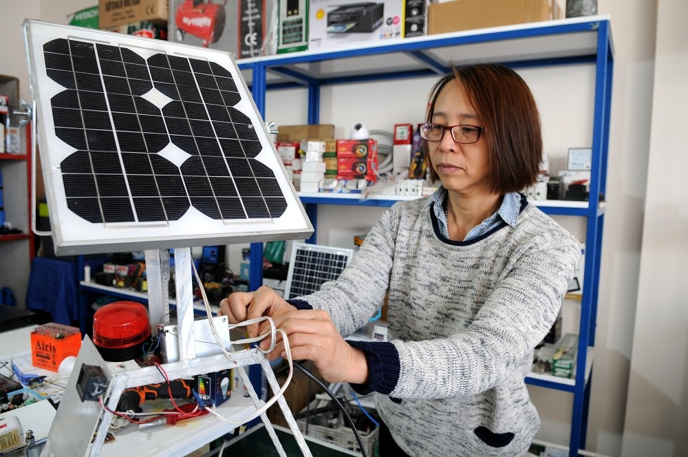 Ying Saru0131 connects a solar panel to a converter in her shop in Bingu00f6l, Feb. 15, 2019.