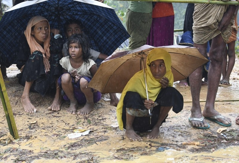 In this file photo taken on September 17, 2017 Rohingya refugees protect themselves from rain in Balukhali refugee camp near the Bangladesh town of Gumdhum (AFP File Photo)