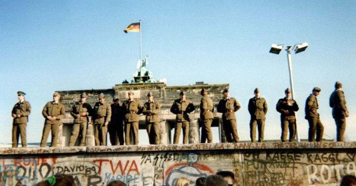 East German border guards stand on a section of the Berlin Wall, with the Brandenburg gate in the background, Berlin, Nov. 11, 1989. (AFP)