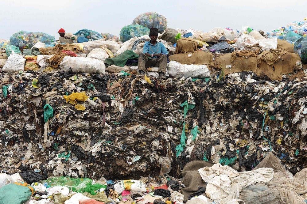 A man sits on waste at the Ngong town dumping site, 30 kilometers southwest of Nairobi.