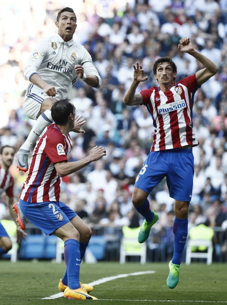 Real Madridu2019s Portuguese striker Cristiano Ronaldo (L) tries to score next to Uruguayan defender Diego Godin (C) of Atletico Madrid during the Primera Division match at Santiago Bernabeu stadium in Madrid on Apr. 8.