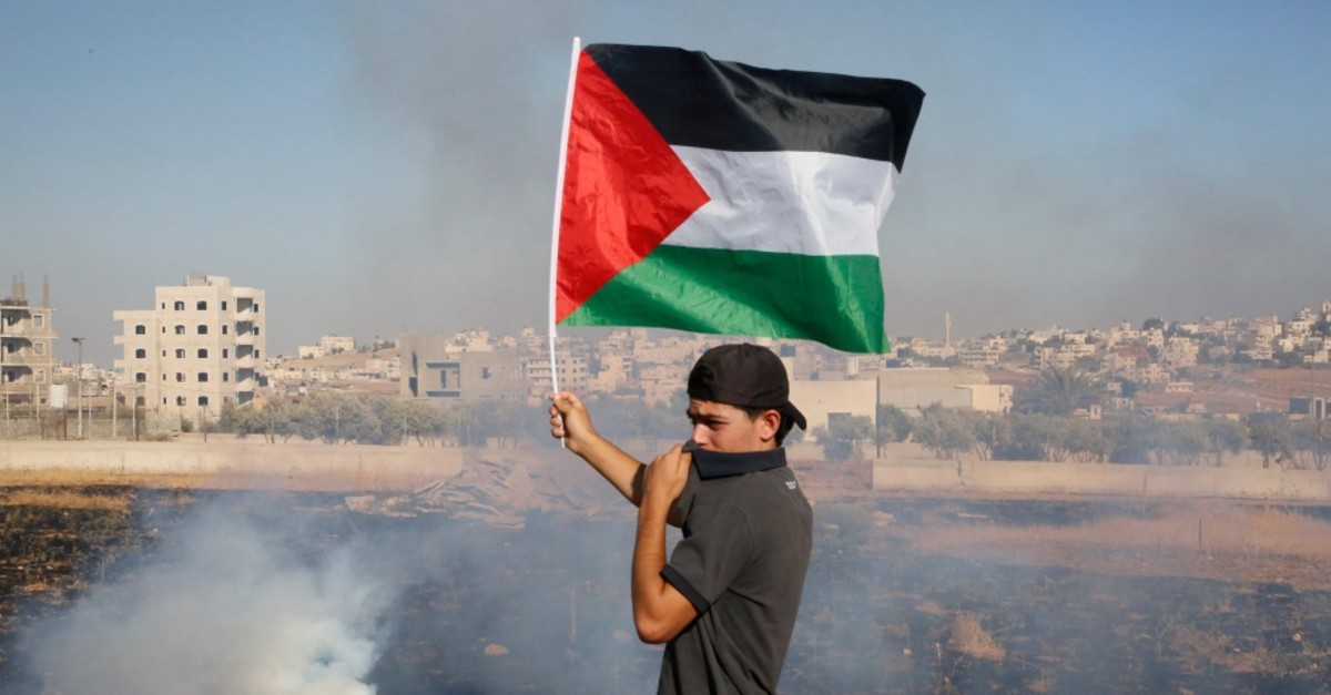 A Palestinian teen waves the national flag as he covers his face from tear gas fired by Israeli soldiers during a demonstration against the Israeli state demolishing civilian buildings in the Palestinian village of Beit Sahur in the occupied West Ban
