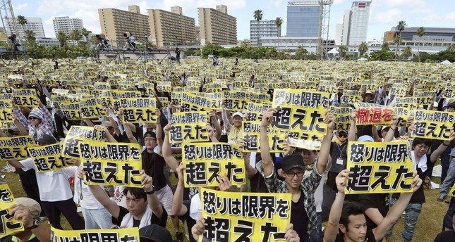 Protesters hold placards that read: Our anger has reached its limit during a protest rally against the presence of U.S. military bases.