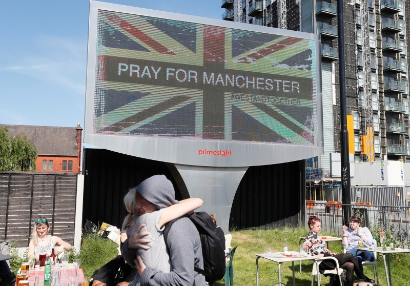 In this Tuesday May 23, 2017 file photo, couple embrace under a billboard in Manchester, England, the day after the suicide attack at an Ariana Grande concert that left more than 20 people dead. (AP Photo)