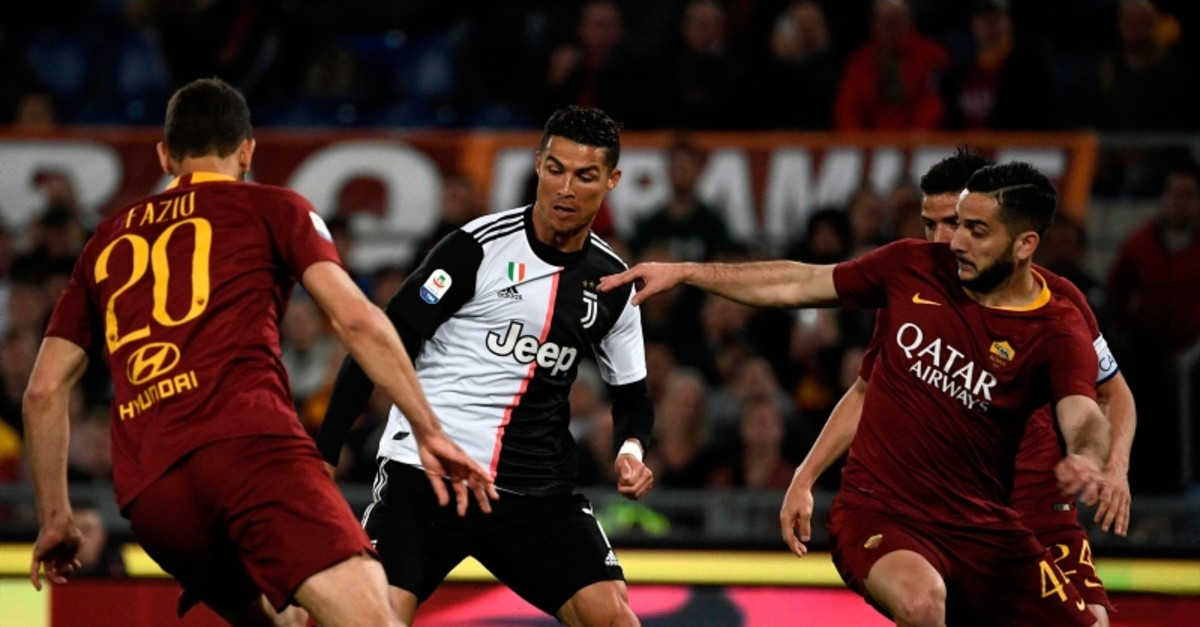 Juventus forward Cristiano Ronaldo (C) vies with Roma defenders Federico Fazio of Argentina (L) and AS Roma Greek defender Konstantinos Manolas during the Italian Serie A football match at the Olympic stadium in Rome, on May 12, 2019. (AFP Photo)