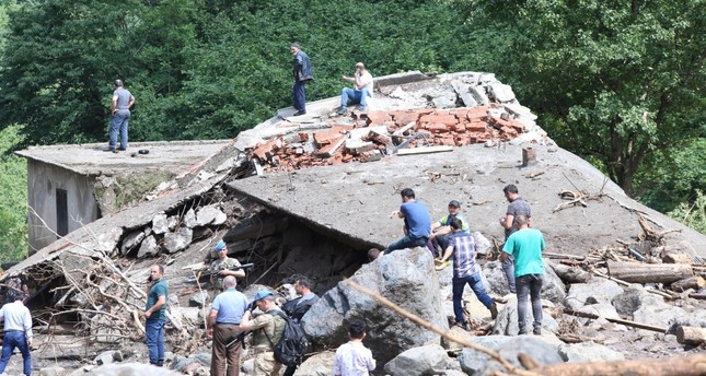 People stand around a building wrecked by rocks carried by flash floods in Araklı, Trabzon, June 19, 2019.