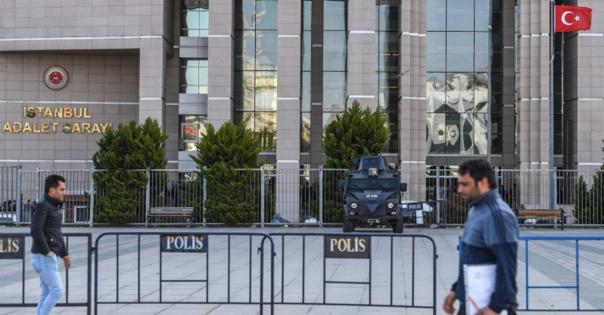 People walk past an armed Turkish police vehicle standing outside the courthouse in Istanbul on March 28, 2019, during the trial of Metin Topuz, a US consulate staffer accused of spying and attempting to overthrow the government. (AFP Photo)